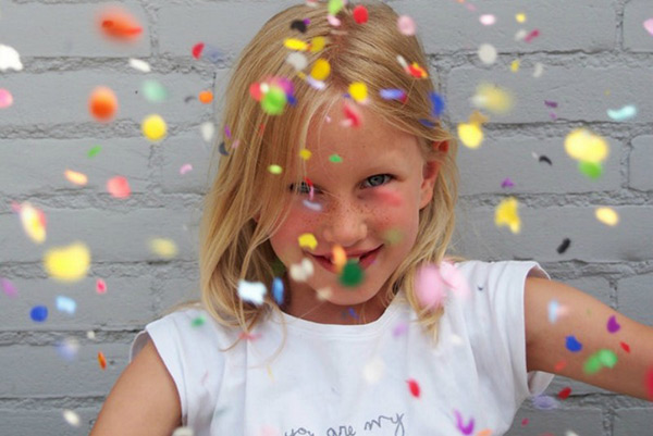 little girl with confetti in the air